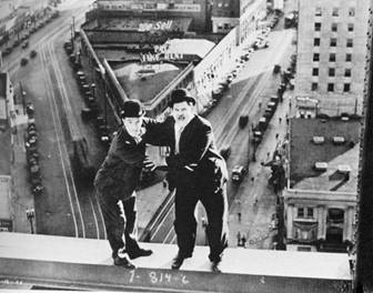 Laurel and Hardy teetering on a girder high above a city street.